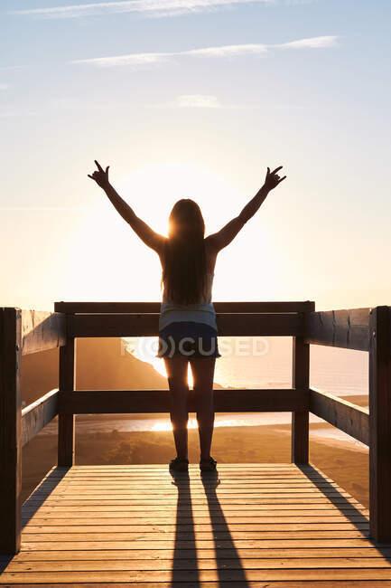 Вид женщины-туристки, стоящей на деревянной террасе и восхищающейся живописным пейзажем бесконечного моря на закате — стоковое фото
