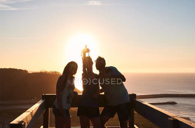 Turistas sonrientes apoyados en barandillas de madera y tomando autorretrato contra el cielo al atardecer sobre el mar tranquilo - foto de stock