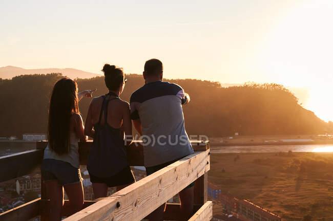 Полный вид сзади туристов, стоящих на деревянной платформе и любующихся спокойным морем во время заката — стоковое фото