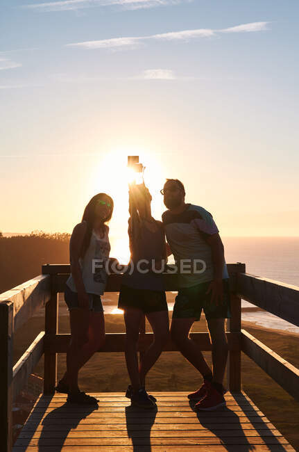 Smiling tourists leaning on wooden railing and taking self portrait against sunset sky over calm sea — Stock Photo