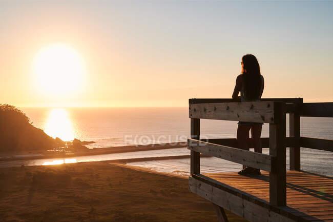 Полный вид на тело женщины-туристки, стоящей на деревянной террасе и любующейся живописными пейзажами бесконечного моря на закате — стоковое фото