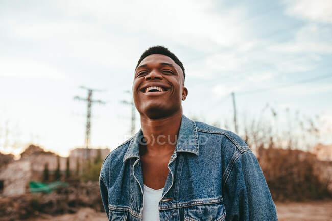 Молодий афроамериканець з сучасною зачіскою в джинсовій куртці дивиться на камеру під хмарним небом. — стокове фото