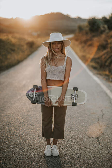 Full body content young female in casual wear and summer hat holding cruiser skateboard and looking at camera while standing on empty asphalt road in rural area at sunset — Stock Photo