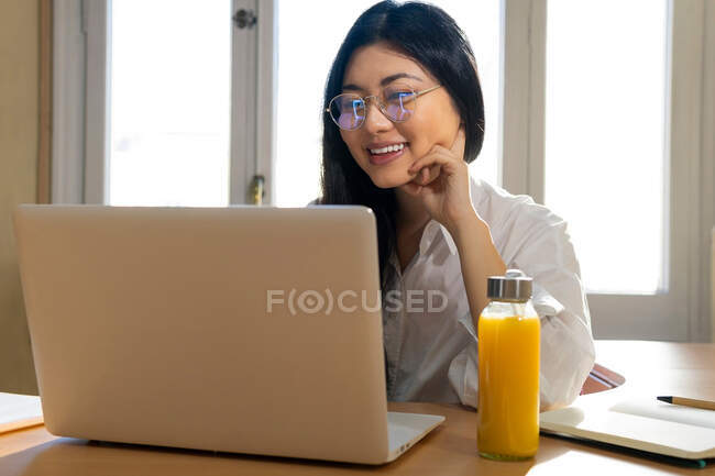 Happy ethnic female self employed freelancer in eyeglasses working on laptop at home — Stock Photo