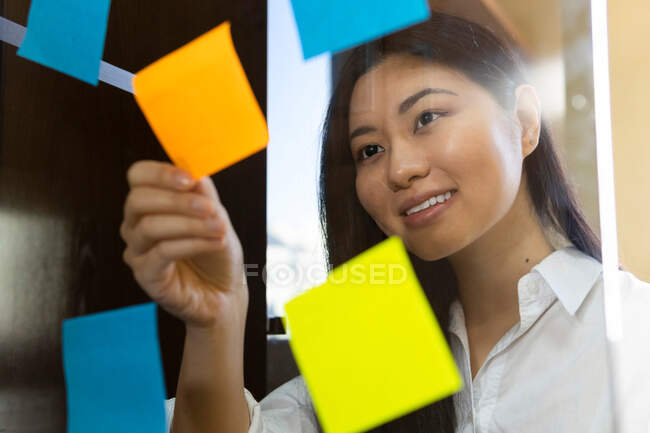 Young glad ethnic female entrepreneur arranging colorful paper stickers on transparent surface in office in daytime — Stock Photo