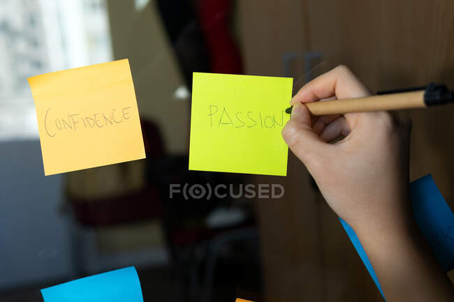 Crop anonymous executive taking notes on bright paper stickers with Passion and Confidence inscriptions on glass wall in office — Stock Photo