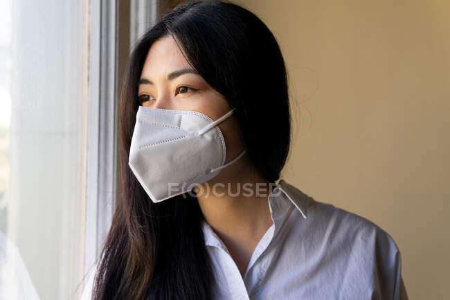 Visão lateral da jovem executiva étnica em máscara respiratória olhando para a janela no espaço de trabalho — Fotografia de Stock
