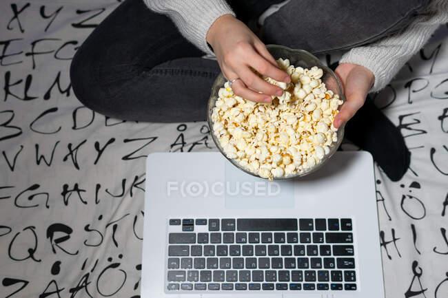 Dall'alto del raccolto anonimo adolescente in abiti casual mangiare popcorn mentre si guarda il film su netbook a casa — Foto stock