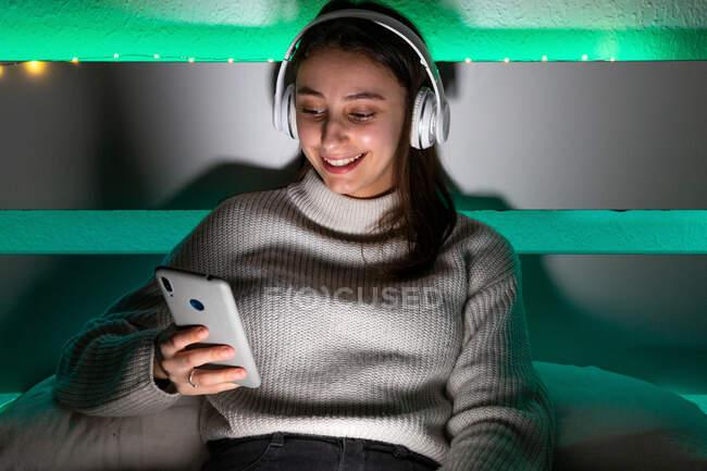 Обрезание очаровательной женщины в свитере слушать музыку с наушниками во время просмотра мобильного телефона на кровати — стоковое фото