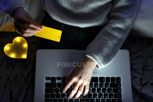 From above of crop unrecognizable teen in sweater typing credit card data on keyboard of netbook while shopping online — Stock Photo