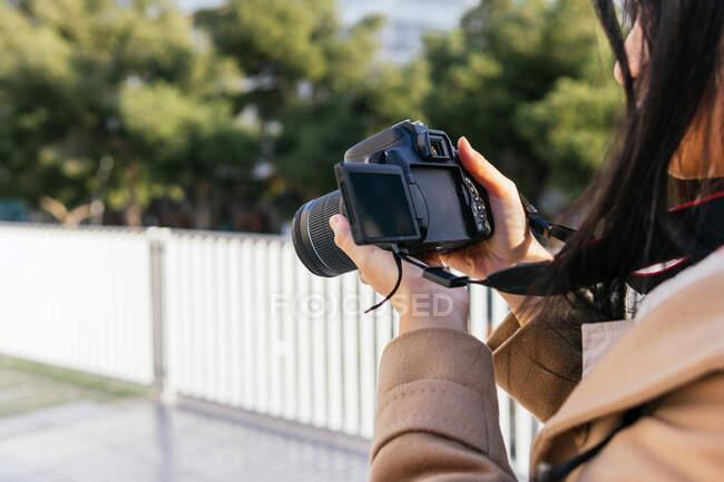 Recortado fotógrafa irreconocible fotografía de fotos en la cámara de fotos profesional en la calle de la ciudad - foto de stock