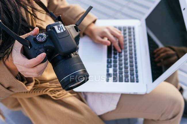 Desde arriba recortado fotógrafa irreconocible usando ropa interior caliente netbook de navegación mientras trabaja de forma remota - foto de stock