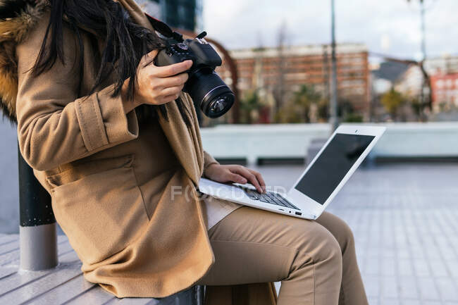 Side view of cropped unrecognizable female photographer wearing warm outerwear browsing netbook while working remotely — Stock Photo