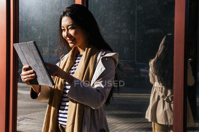 Fröhliche Asiatinnen stehen vor spiegelnder Wand und stöbern bei sonnigem Wetter auf dem Bürgersteig — Stockfoto
