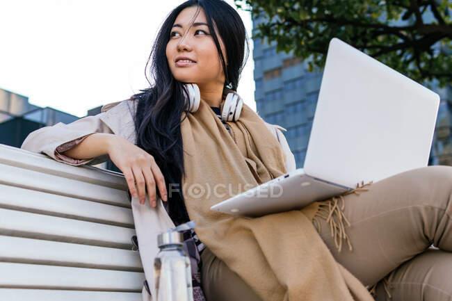Junge Asiatinnen in warmer Oberbekleidung blättern im Netbook, während sie ferngesteuert auf einer Bank auf der Straße arbeiten — Stockfoto