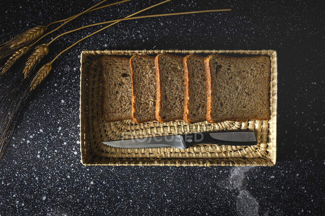 Top view of fresh homemade rye bread near knife in wicker basket and wheat spikes on table — Stock Photo