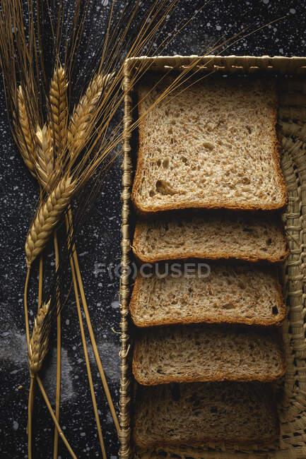 Vista superior do pão de centeio caseiro fresco perto da faca na cesta de vime e picos de trigo na mesa — Fotografia de Stock