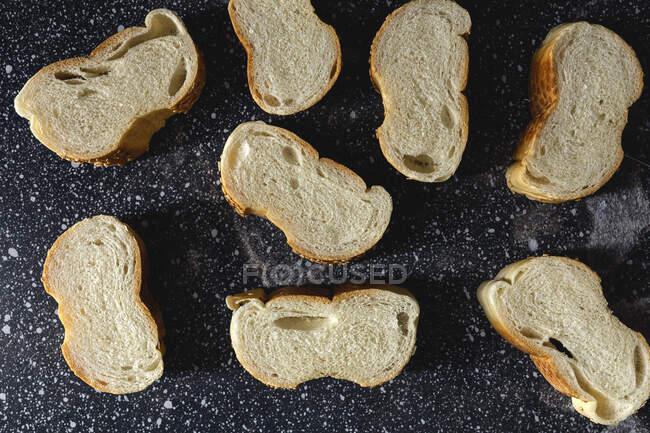 Vista superior de pedaços de pão branco perto de faca e picos de trigo na tábua de madeira — Fotografia de Stock
