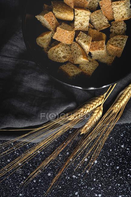 Pedaços de pão crocante na tigela perto de picos de trigo em têxteis pretos no quarto — Fotografia de Stock