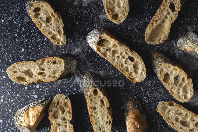 De cima de pão crosty apetitoso perto de picos de trigo e tecido escuro na mesa — Fotografia de Stock