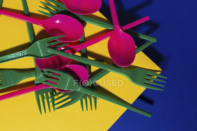 Vista aérea de cubiertos ecológicos de colores brillantes cerca de la hoja de cartón amarillo - foto de stock