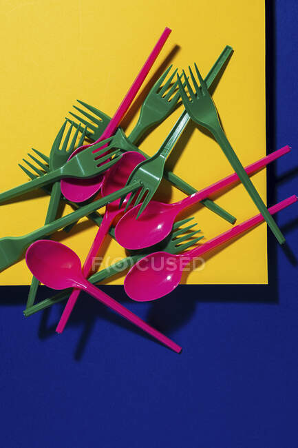 Overhead view of bright colorful eco friendly cutlery near yellow carton sheet — Stock Photo