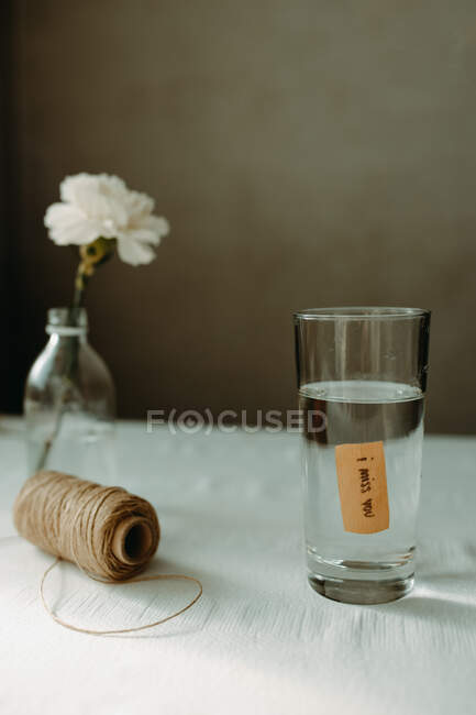 Water pouring into glassware with inscription i miss you placed near skein of thread and blooming carnation — Stock Photo