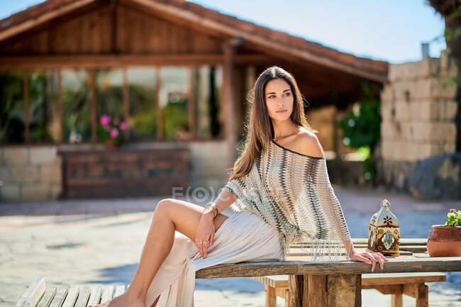 Joven turista contemplativa descansando sobre una mesa de madera contra una casa envejecida mientras mira hacia otro lado iluminada - foto de stock