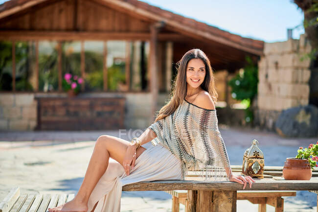 Young contemplative female tourist resting on wooden table against aged house while looking away in back lit — Stock Photo