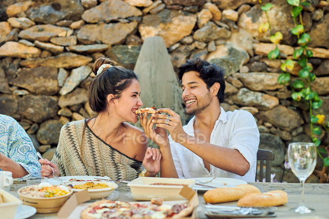 Young content ethnic man feeding girlfriend with tasty slice of pizza while sitting at table near crop anonymous partner outdoors — Stock Photo