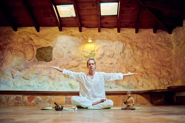 Молодой концентрированный самец с закрытыми глазами сидит в позе Падмасаны, практикуя йогу возле статуэтки Будды — стоковое фото