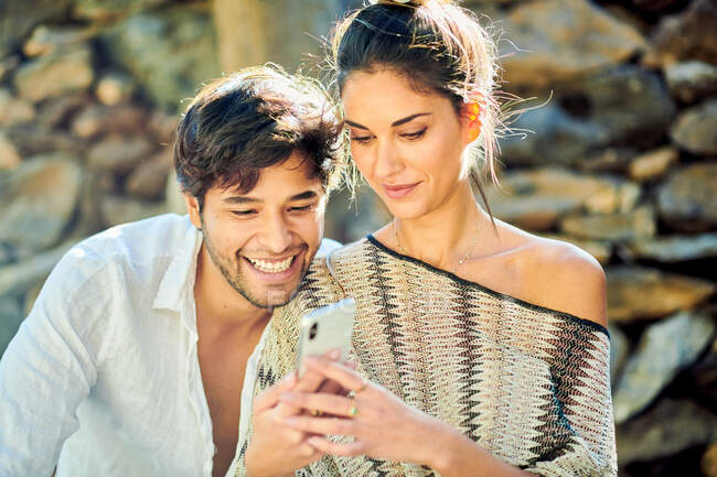 Smiling bearded ethnic man with crop girlfriend surfing internet on cellphone against stone wall in back lit — Stock Photo