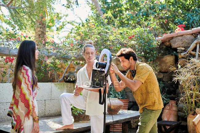 Joven hombre étnico con cámara fotográfica digital cerca de la pareja con la grabación de vídeo portátil de habla femenina para vlog en el jardín - foto de stock