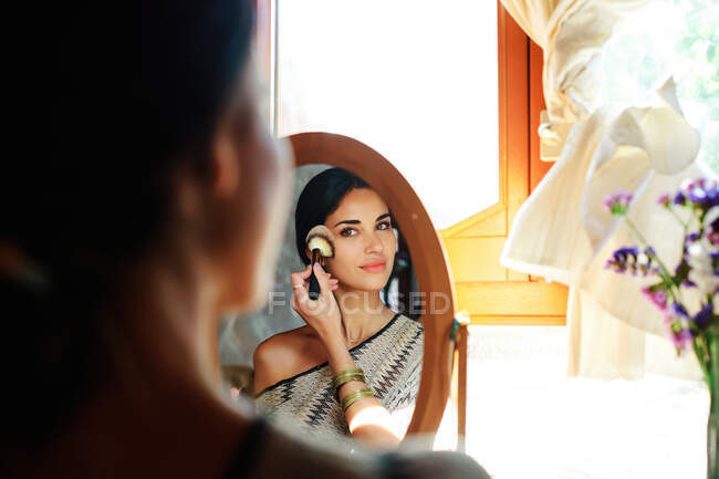 Back view of crop young tender female applying blush with brush while looking in mirror at home — Stock Photo