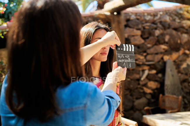 Crop anonymous female assistant with clapboard near actress preparing for filmmaking on sunny day — Stock Photo