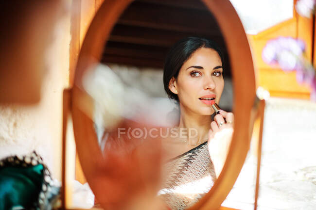 Crop young gentle female making up lips with lipstick while looking in mirror in sunlight — Stock Photo