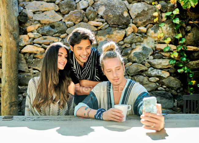 Young glad multiethnic partners taking self portrait on photo camera at table against climbing plants in courtyard — Stock Photo