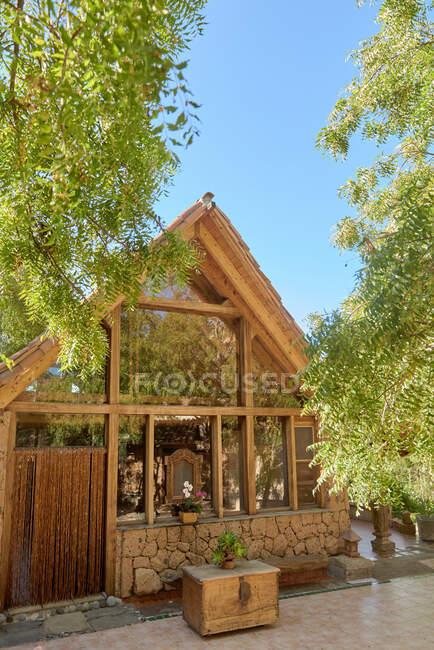 Возрастной экстерьер здания между заросшими зелеными деревьями в саду под голубым небом при дневном свете — стоковое фото