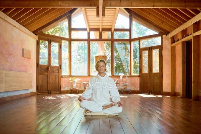 Молодой внимательный мужчина босиком сидит в позе лотоса на подушке с закрытыми глазами, практикуя йогу на полу рядом со статуэткой Будды и босиком. — стоковое фото