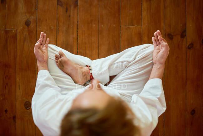 Из выше урожая анонимный мужчина в белой одежде делает жест мудры руками, практикуя йогу в доме — стоковое фото