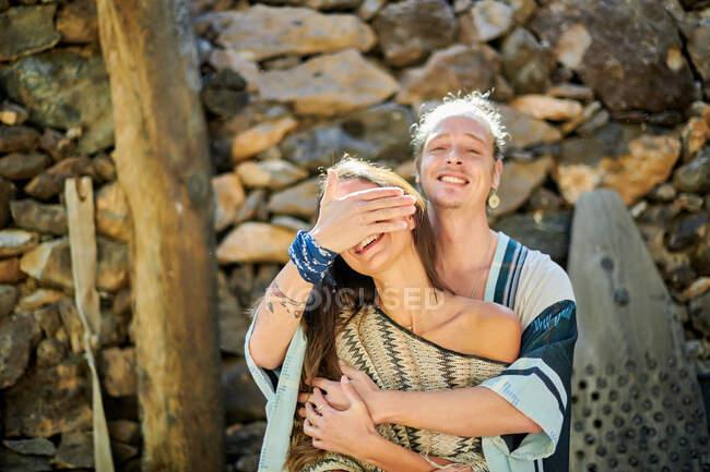 Joven macho sonriente abrazando y cubriendo la cara de una hembra irreconocible amada mientras mira a la cámara con la espalda iluminada - foto de stock