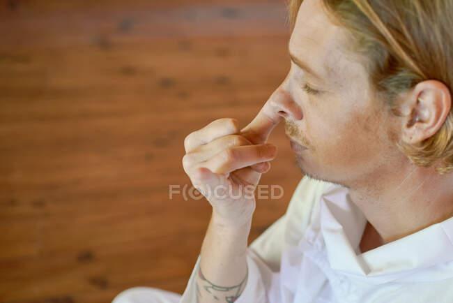 De cima vista lateral da colheita jovem mindful masculino no desgaste branco com os olhos fechados praticando respiração narina em parquet — Fotografia de Stock