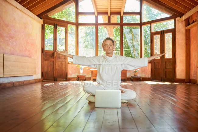 Молодой сконцентрированный мужчина сидит с закрытыми глазами и скрещенными ногами, практикуя йогу против нетбука в комнате для медитации — стоковое фото