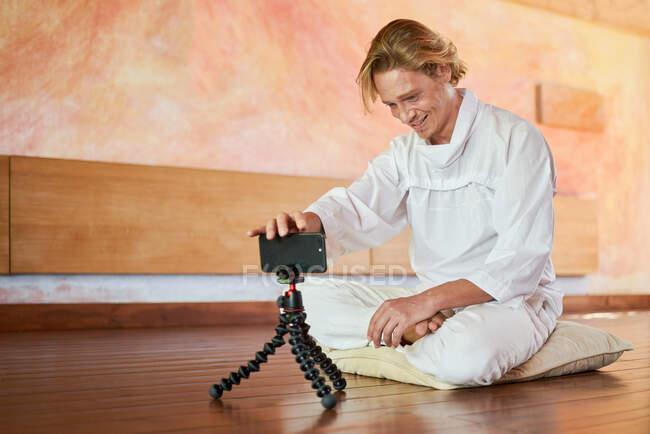 Jovem macho alegre em vestuário branco com celular sentado com pernas cruzadas no travesseiro no salão da casa — Fotografia de Stock