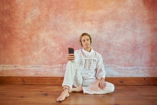 Молодий уважний чоловік у білому одязі з мобільним телефоном, який сидить на стіні і слухає курс йоги від голови до голови. — стокове фото