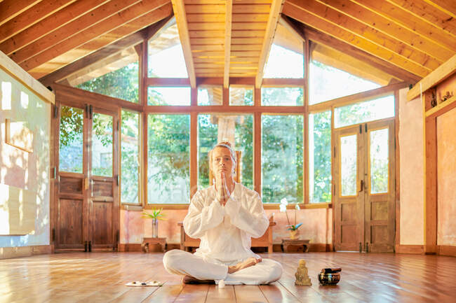 Young mindful male barefoot male sitting in lotus pose practicing yoga on floor near bowl gong and Buddha statuette — Stock Photo