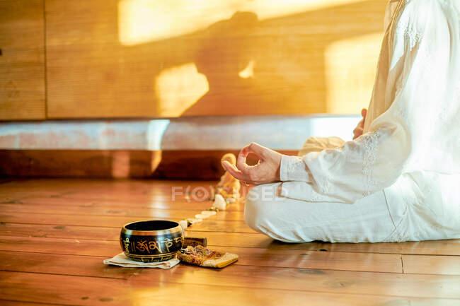 Побочный вид на неузнаваемую босоногую самку, практикующую йогу на полу возле чашечного гонга и статуэтки Будды — стоковое фото