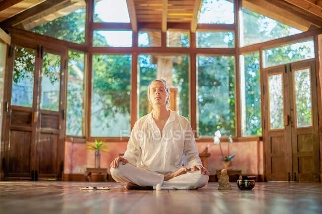Молодой внимательный мужчина босиком сидит в позе лотоса и практикует йогу на полу рядом со статуэткой Будды и чашечкой. — стоковое фото