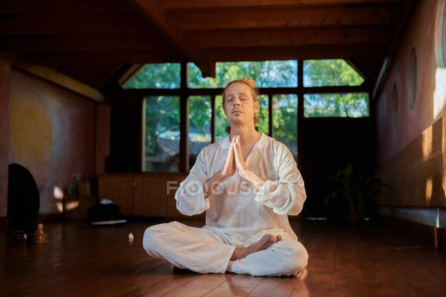 Молодой внимательный мужчина босиком сидит в позе лотоса с закрытыми глазами, практикуя йогу на полу рядом со статуэткой Будды и чашечкой. — стоковое фото