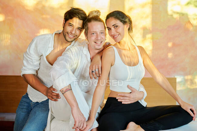 Smiling multiracial couple sitting close to reiki master and embracing each other in  alternative medicine salon — Stock Photo